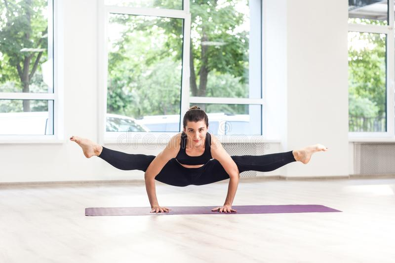 Full lenght portrait of young adult gumnastics beautiful woman in black pants and top is doing hand stand split, practicing yoga. Exercises. Indoor, studio shot stock photography