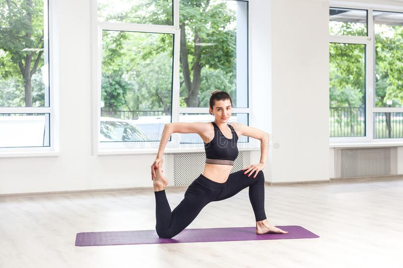 Full lenght portrait of young adult sporty attractive woman in black pants and top is doing horse rider exercise, anjaneyasana. Pose, working out, indoor, yoga royalty free stock image
