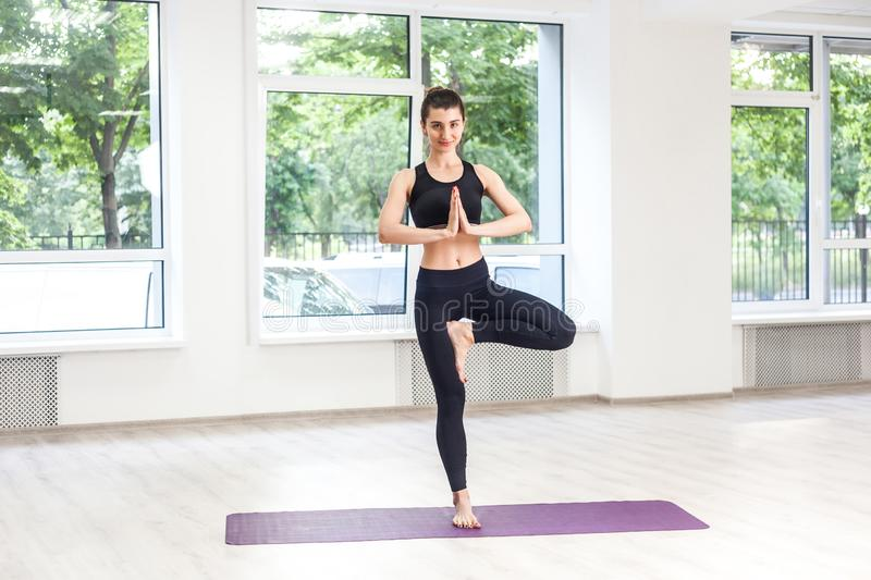 Full lenght portrait of young adult sporty attractive woman in black pants and top is practicing yoga, doing balance exercise,. Tree pose and vrksasana, indoor royalty free stock images
