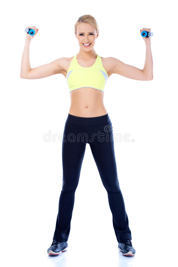 Full lenght shoot of sporty female with dumbbell