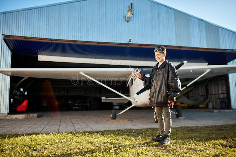 Full lenght view of adorable kid, playing outside aircraft hangar with toy plane royalty free stock photo