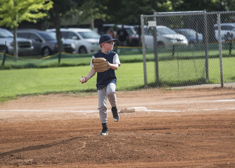Full length Action photo of a Little League baseball pitcher throwing a pitch. Young boy with glasses focused on winning stock images