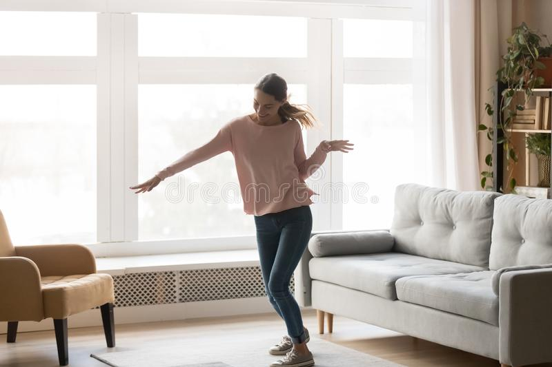 Full-length of active young woman dancing in living room stock photography
