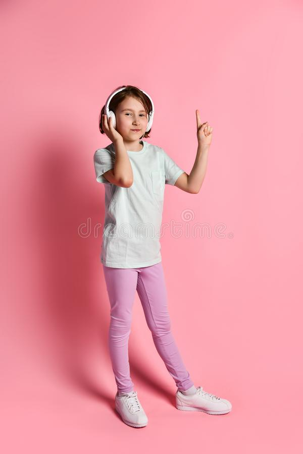 Full-length  girl of music listens in white headphones, enjoying the pleasure of listening to music against a pink background royalty free stock images