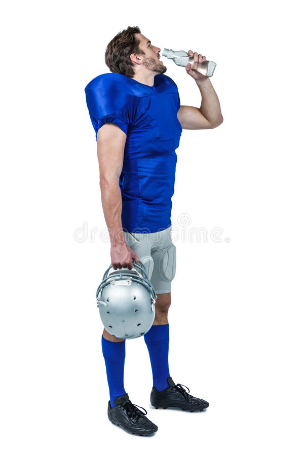 Full length of American football player holding helmet while drinking water stock photo
