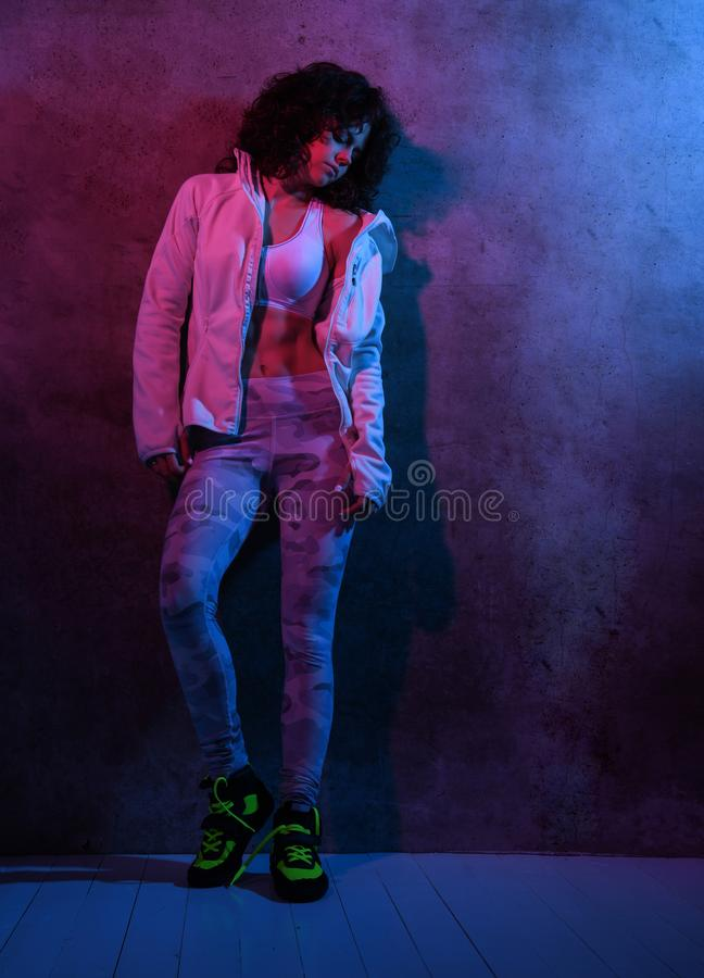 Full length of an attractive fit woman or sports trainer in sportswear posing on camera near a concrete wall royalty free stock photos