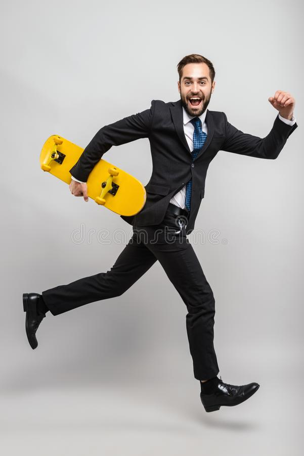Full length of an attractive smiling young businessman. Wearing suit isolated over gray background, carrying skateboard, running stock photography