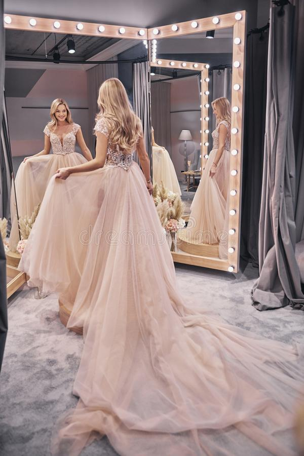 Looks just right. Full length of attractive young woman trying on wedding dress while standing in front of the mirror in bridal shop stock images