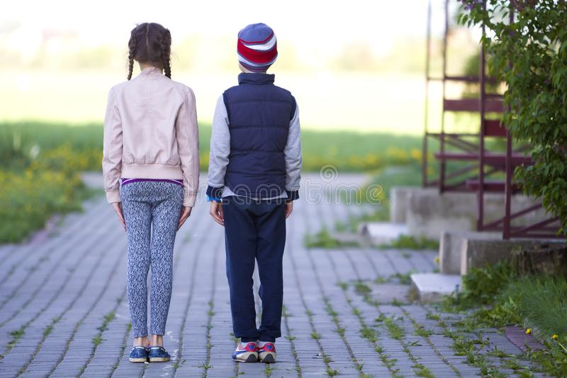 Full length back view of two children, girl with long braids and boy in casual clothing standing very straight on grassy pavement royalty free stock image