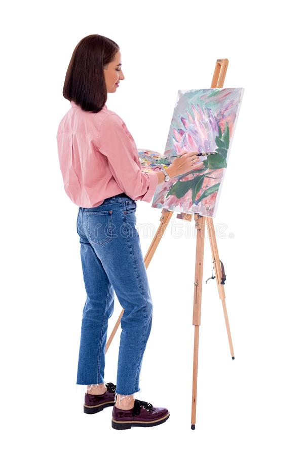 Full length back view of young woman artist with easel, palette and paint brush painting picture isolated on white. Background royalty free stock image