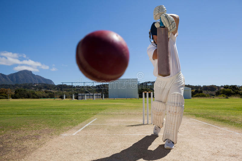 Full length of batsman playing cricket on pitch against blue sky stock photography