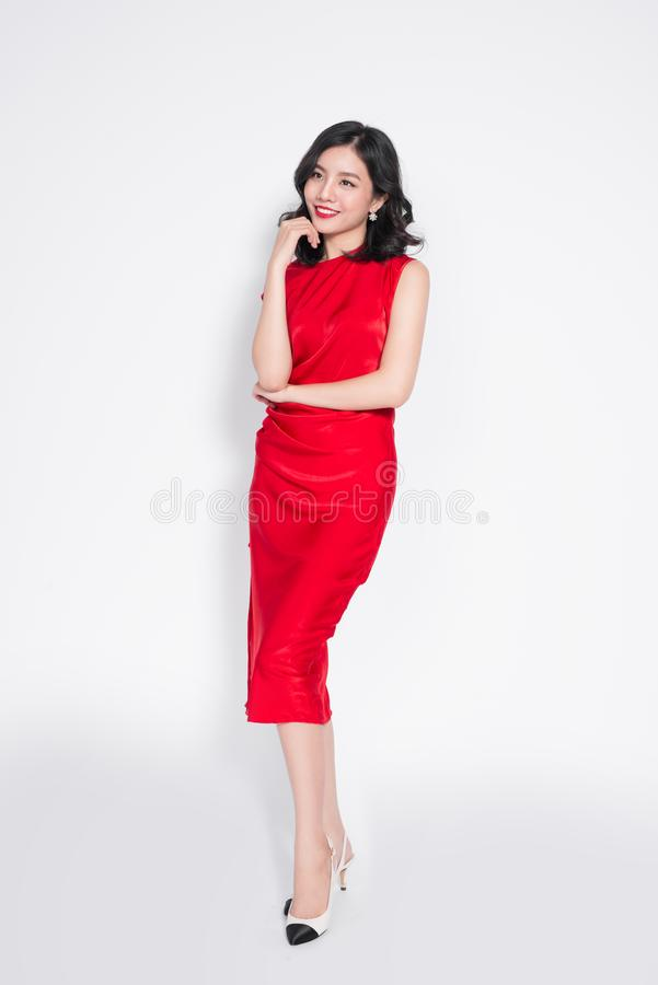 Full length of beautiful asian woman in dress standing and posing over white background royalty free stock photo