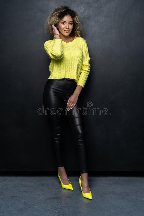 Full length of a beautiful black female fashion model with curly hair over black background. stock photo