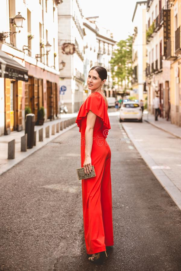 Full length of beautiful brunette young woman with topknot hairstyle smiling and wearing red ruffles dress posing on the street. Full length of beautiful royalty free stock image