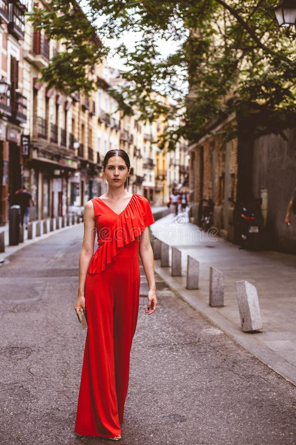 Full length of beautiful brunette young woman with topknot hairstyle smiling and wearing red ruffles dress walking on the street. Full length of beautiful stock photo
