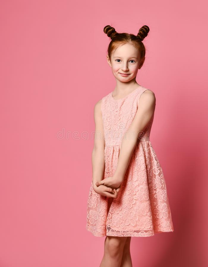 Full length of beautiful little girl in dress standing and posing over pink background royalty free stock photography
