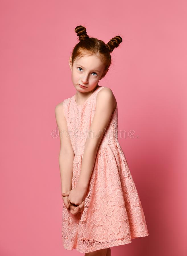 Full length of beautiful little girl in dress standing and posing over pink background stock image