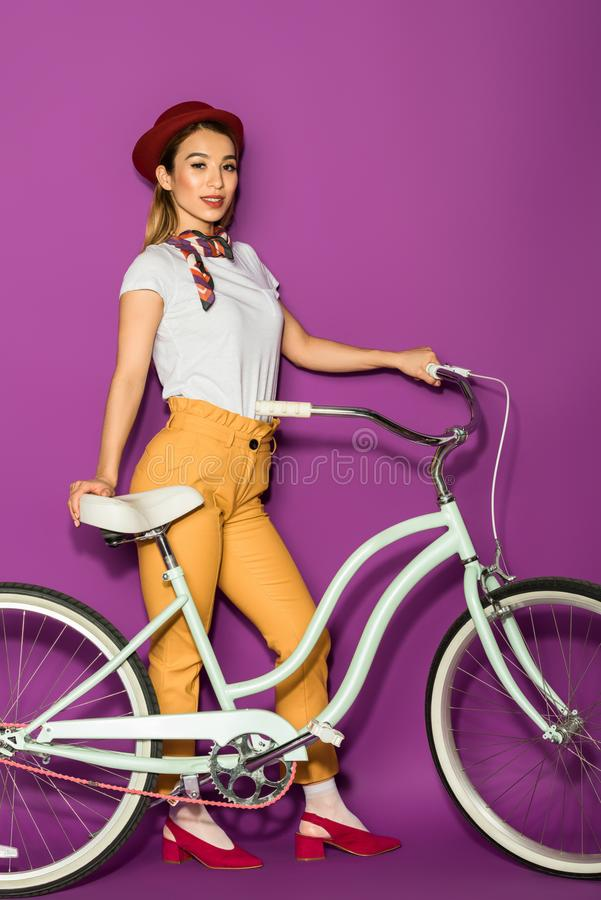 full length of beautiful stylish asian woman standing with bike and smiling at camera stock photo