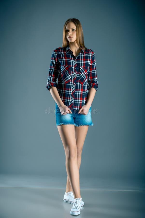 Full length beautiful teen girl in plaid shirt and denim shorts stock image