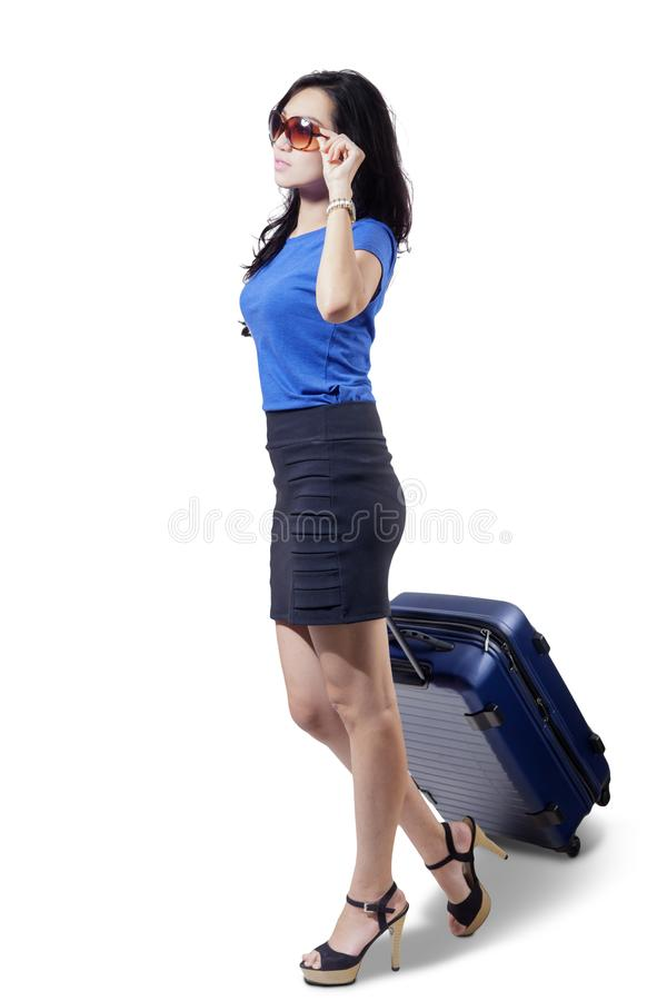 Beautiful woman pulling a luggage on studio royalty free stock photography
