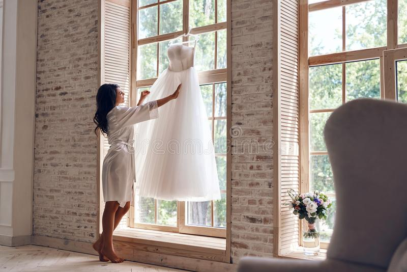 Looks just right. Full length of beautiful young woman in silk bathrobe touching her wedding dress while standing near the window royalty free stock photos
