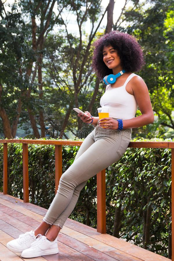 Full length body portrait of black girl holding cell phone and cup of juice. Woman smiling and leaning against railing. Wooded royalty free stock photos