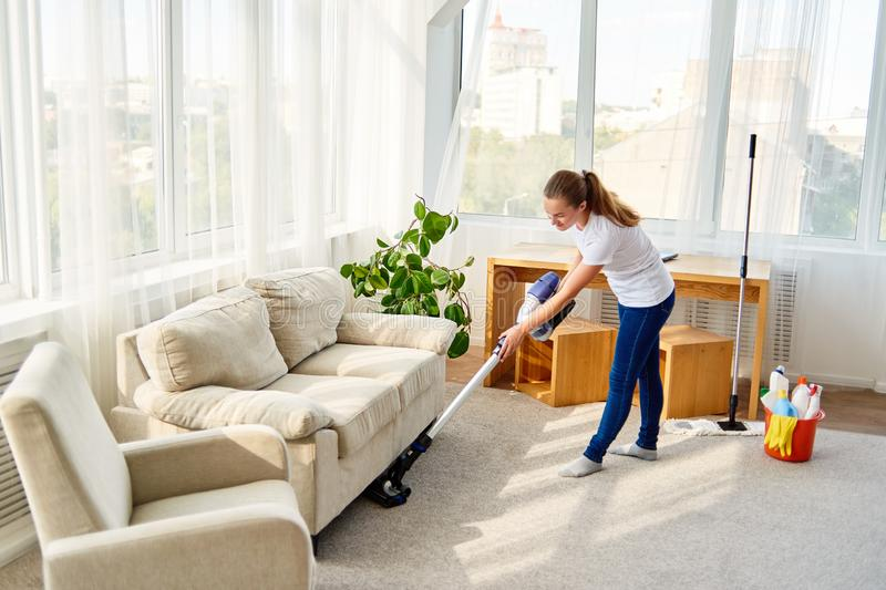 Full length body portrait of young woman in white shirt and jeans cleaning carpet with vacuum cleaner in living room, copy space. stock photo