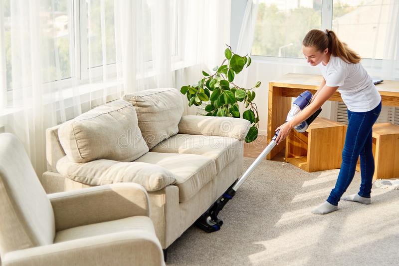Full length body portrait of young woman in white shirt and jeans cleaning carpet with vacuum cleaner in living room, copy space. royalty free stock photos