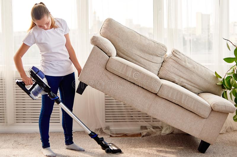 Full length body portrait of young woman in white shirt and jeans cleaning carpet with vacuum cleaner under sofa in living room. stock images