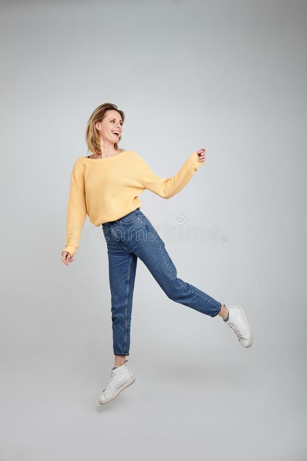 Full length body shot of joyful pleased young female model jumps happily in air against white background, wears, sweatshirt, jeans royalty free stock photos