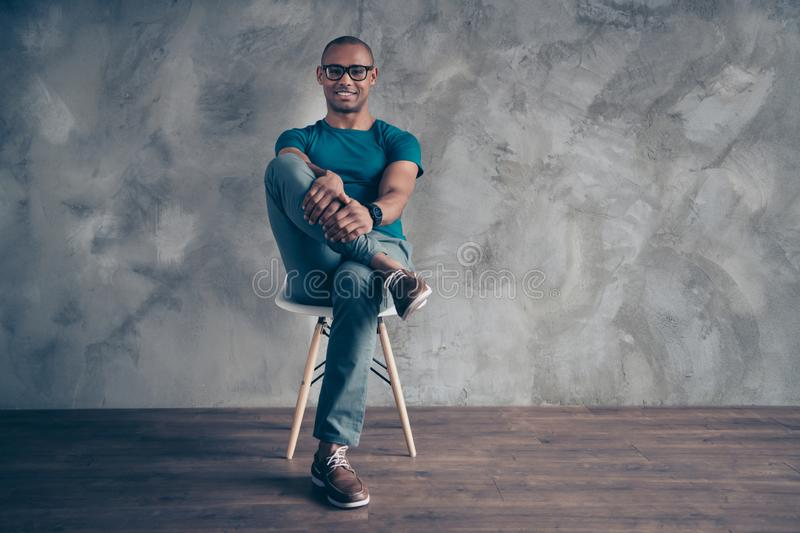 Full length body size photo amazing he him his dark skin macho handsome sit cozy chair hold arms hands leg wait turn. Interview work job wear specs casual blue stock photos