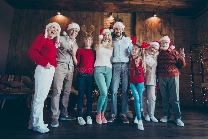 Full length body size photo of cheerful positive cute nice family with granddad and siblings showing v-signs in antlers royalty free stock photography