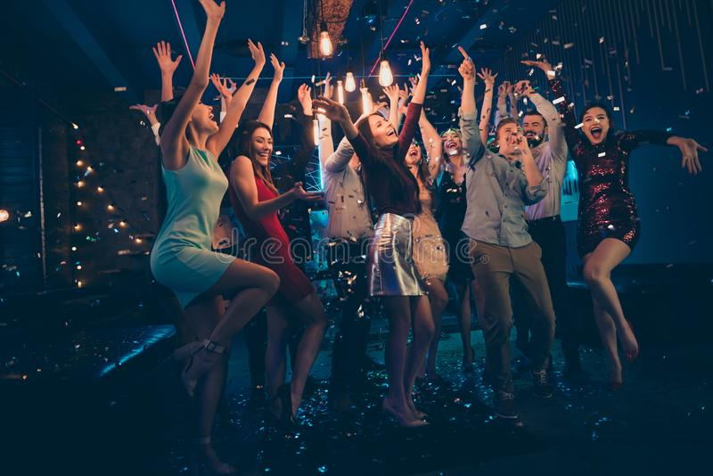 Full length body size photo of company dancing cheerfully at night club under falling confetti and light of shining. Full length body size photo of company royalty free stock image