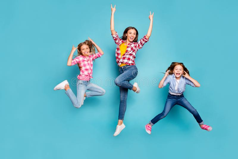 Full length body size photo of funky funny excited trendy family who are rock fans jumping joyfully wearing jeans denim stock image