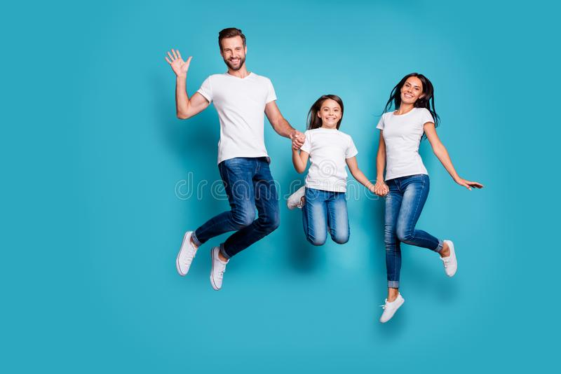 Full length body size photo of funny funky cheerful glad family jumping in front of camera while isolated with blue stock photo