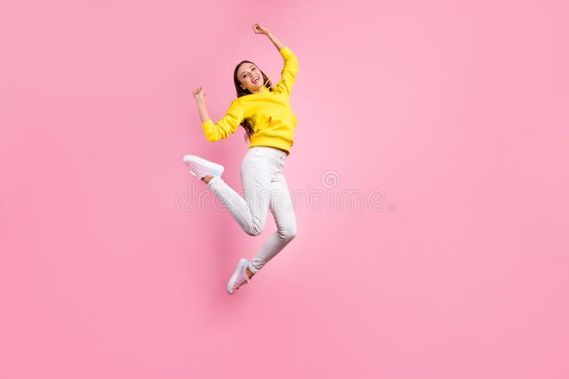 Full length body size photo of jumping cute charming attractive gorgeous girlfriend rejoicing with something positive. Full length body size photo of jumping stock image