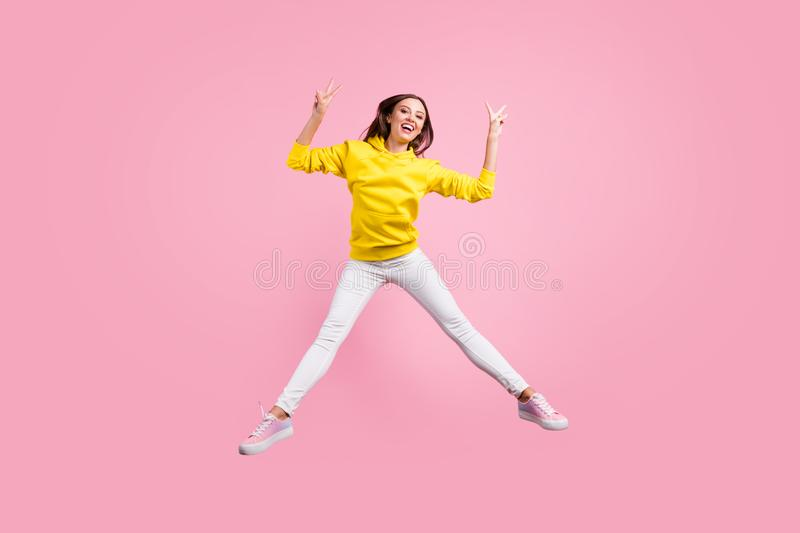 Full length body size photo of jumping cute nice charming attractive girlfriend showing you v-sign wearing yellow. Full length body size photo of jumping cute royalty free stock photo