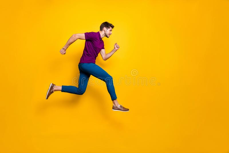 Full length body size side profile photo of fast quick handsome man wearing blue pants trousers footwear running jumping. Full length body size side profile stock photo