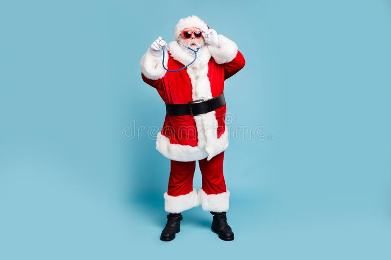 Full length body size view of his he nice funky bearded Santa Claus wearing phonendoscope making diagnostic. Full length body size view of his he nice funky stock images