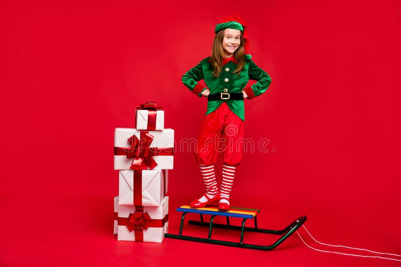 Full length body size view of nice attractive cheerful cheery glad funny pre-teen elf standing on sled fairy miracle stock image