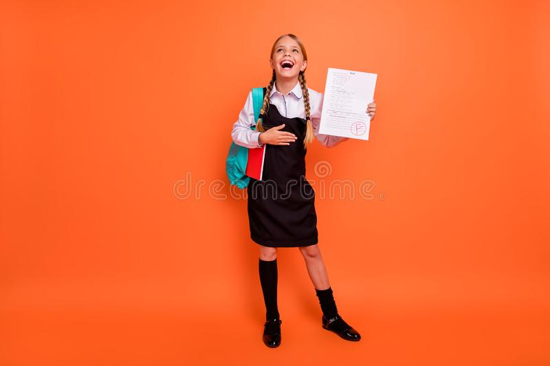 Full length body size view of nice attractive lovely cheerful cheery glad pre-teen girl holding in hand failure grade royalty free stock photos
