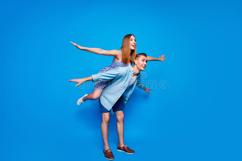 Full length body size view of two nice attractive cheerful cheery glad positive people piggy-backing having fun jet pack. Full length body size view of two nice stock images