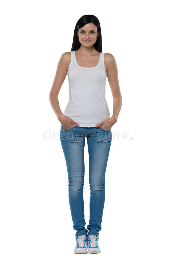 Full length of a brunette woman in a white tank top and jeans. royalty free stock photos