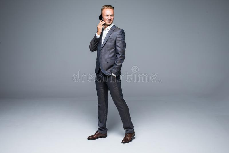 Full length business man in black suit moves with hand in pocket and talking at phone. Isolated gray background. Full length business man in black suit moves stock image