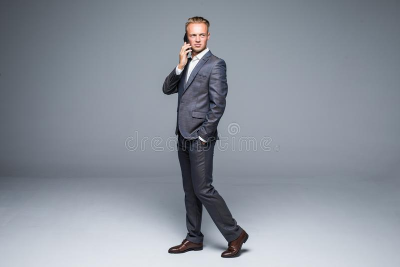 Full length business man in black suit moves with hand in pocket and talking at phone. Isolated gray background. Full length business man in black suit moves royalty free stock images