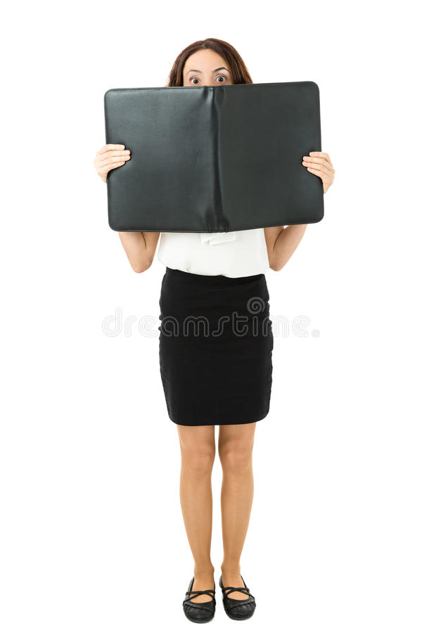 Full length business woman looking from behind a folder royalty free stock images
