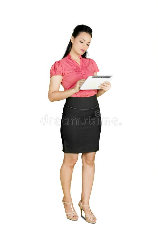 Business woman using tablet while standing royalty free stock image