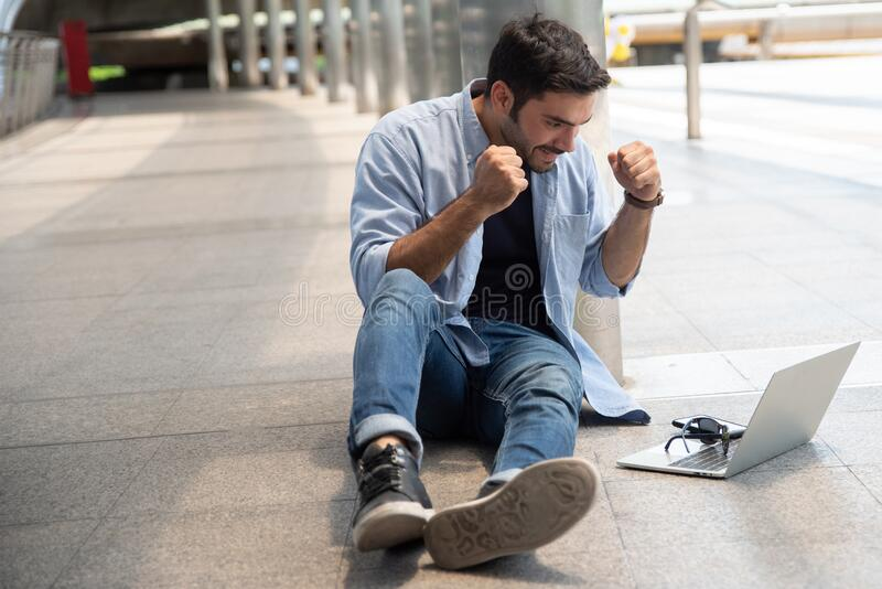 Full Length Of Businessman Using Laptop While Sitting On Footpath.  stock photography