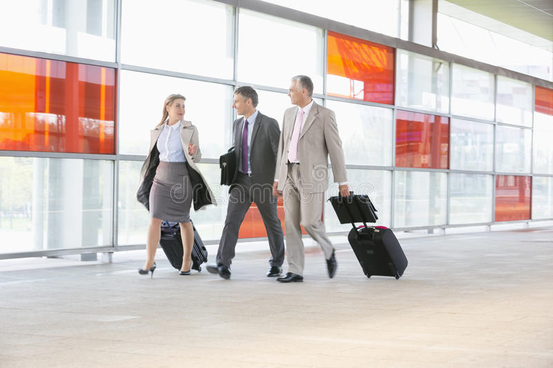Full length of businesspeople with luggage walking on railroad platform royalty free stock image