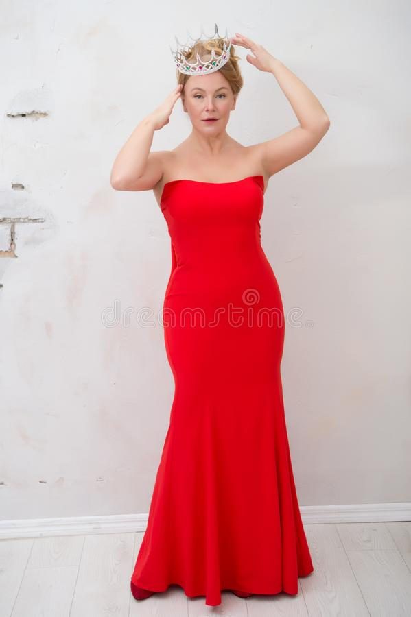 Full length of charismatic blonde woman wearing elegant red dress and silver crown royalty free stock photography